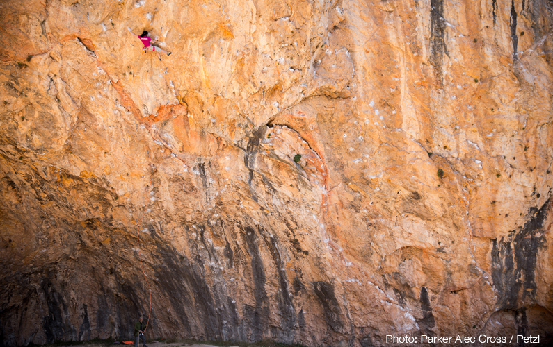 Ashima Shiraishi sending Open Your Mind Direct (9a/+), belayed by her father, in Santa Linya cave. Photo: Parker Alec Cross / Petzl